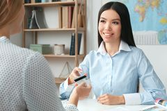 Jeune consultant en matière féminin d'agent de voyage à l'agence de visite avec un paiement de client image libre de droits