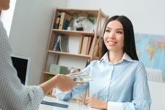 Jeune consultant en matière féminin d'agent de voyage à l'agence de visite avec un paiement en espèces de client image libre de droits