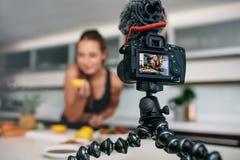 Jeune contenu femelle d'enregistrement de blogger pour le videoblog dans la cuisine image stock