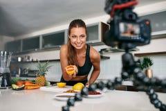 Jeune contenu femelle d'enregistrement de blogger pour le videoblog dans la cuisine photos stock