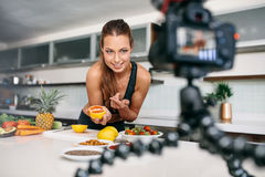 Jeune contenu femelle d'enregistrement de blogger pour le videoblog dans la cuisine photos libres de droits