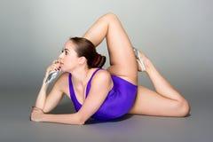 Jeune contorsionniste féminin dans le collant de danseur pourpre sur le fond foncé Image libre de droits