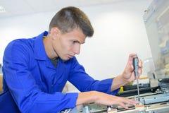 Jeune copieur de photo de bureau de difficulté de technicien image libre de droits