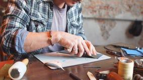 Jeune cordonnier beau coupant le cuir dans l'atelier avec le couteau spécial banque de vidéos