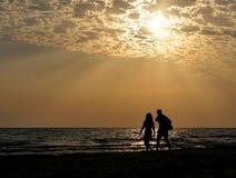 Jeune coucher du soleil de couples en mer Photos libres de droits