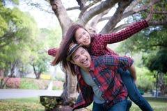 Jeune coupé en parc Ami portant son amie sur pi photo stock