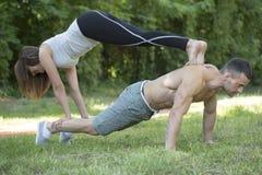 Jeune couples, homme et femme s'exerçant en parc Photographie stock
