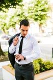 Jeune coupure de prise d'homme d'affaires pour boire le café mais maintenant le regard comment le temps est lui Image libre de droits