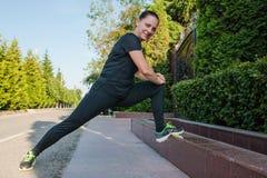 Jeune coureur de femme de forme physique étirant des jambes avant course photographie stock
