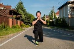 Jeune coureur de femme de forme physique étirant des jambes avant course images stock