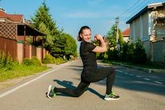 Jeune coureur de femme de forme physique étirant des jambes avant course photos stock