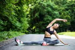 Jeune coureur de femme de forme physique étirant des jambes avant course dans le CIT photo stock