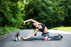 Jeune coureur de femme de forme physique étirant des jambes avant course dans le CIT image stock