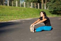 Jeune coureur de femme de forme physique faisant l'étirage avant séance d'entraînement Tir extérieur avec des rayons du soleil L' photo stock