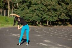 Jeune coureur de fille de forme physique étirant des mains avant séance d'entraînement Tir extérieur avec des rayons du soleil L' photo stock