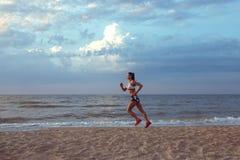 Jeune coureur en bonne santé de traînée de femme de forme physique fonctionnant sur le bord de la mer de lever de soleil images libres de droits