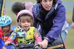 Jeune coureur féminin de bicyclette pendant l'événement de Cycloross Photographie stock