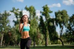 Jeune coureur femelle heureux fonctionnant en parc de ville Femme en bonne santé de forme physique pulsant dehors Image stock