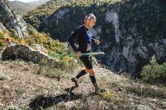 Jeune coureur masculin avec les poteaux de marche fonctionnant par la falaise raide Images stock