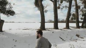 Jeune coureur musculaire pulsant sur la neige près de la route banque de vidéos