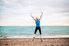 Jeune coureur sportif de femme dans les vêtements de sport bleus sautant sur la plage dehors photographie stock