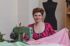 Jeune couturière féminine choisissant le matériel du catalogue dans le studio Photos stock