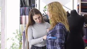 Jeune couturière prenant des mesures de client féminin banque de vidéos