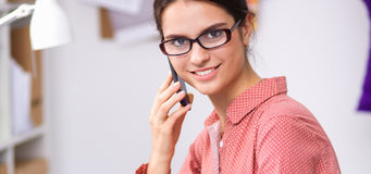 Jeune couturier féminin attirant travaillant au bureau, dessinant tout en parlant sur le mobile Images libres de droits