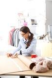 Jeune couturier travaillant dans son studio photo libre de droits