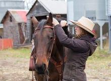Jeune cow-girl étant prête pour un tour de cheval Photographie stock