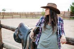 Jeune cow-girl mignonne se penchant sur la barrière de ranch Photo stock