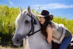 Jeune cow-girl sur le sourire de cheval blanc Photos libres de droits