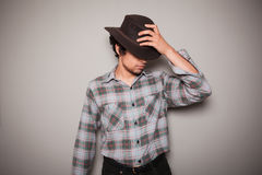 Jeune cowboy dans la chemise de plaid contre un mur vert Photos libres de droits