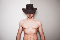 Jeune cowboy sans chemise sur le fond vert et blanc Photographie stock