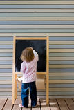 Jeune écriture caucasienne mignonne de garçon sur un tableau noir Image libre de droits