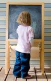 Jeune écriture caucasienne mignonne de garçon sur un tableau noir Photos libres de droits