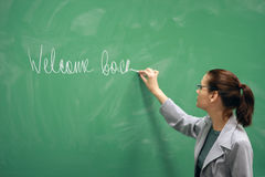 Jeune écriture de professeur sur le panneau Photo stock