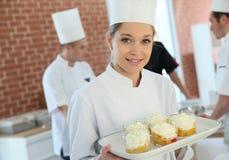Jeune cuisinier de pâtisserie avec des desserts image libre de droits