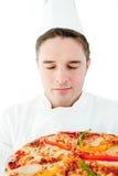 Jeune cuisinier mâle sentant à la pizza avec les yeux fermés Photographie stock