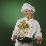 Jeune cuisinier professionnel sur le fond vert - squa Image stock