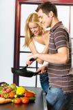 Jeune cuisson heureuse de couples Photos stock