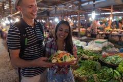 Jeune cuvette de prise de couples avec des légumes faisant des emplettes sur l'homme de sourire heureux et la femme du marché exo Images libres de droits
