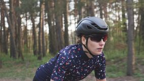 Jeune cycliste féminin mignon sprintant sur la bicyclette hors de la selle visage focalis? Formation de recyclage banque de vidéos