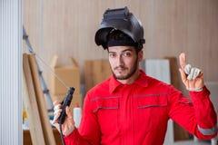 Jeune dépanneur avec une électrode d'arme à feu de soudure et un weldin de casque Photo libre de droits