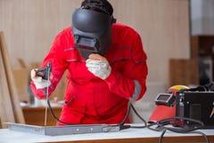 Jeune dépanneur avec une électrode d'arme à feu de soudure et un weldin de casque Photo stock