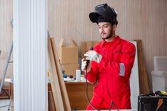 Jeune dépanneur avec une électrode d'arme à feu de soudure et un weldin de casque Images libres de droits