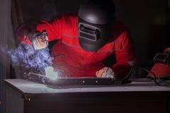 Jeune dépanneur avec une électrode d'arme à feu de soudure et un weldin de casque Photographie stock libre de droits