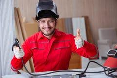 Jeune dépanneur avec une électrode d'arme à feu de soudure et un weldin de casque Photos stock