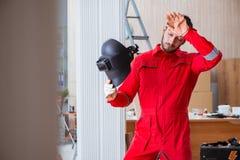 Jeune dépanneur avec une électrode d'arme à feu de soudure et un weldin de casque Images stock