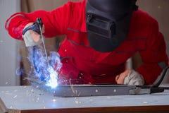 Jeune dépanneur avec une électrode d'arme à feu de soudure et un weldin de casque Photos libres de droits